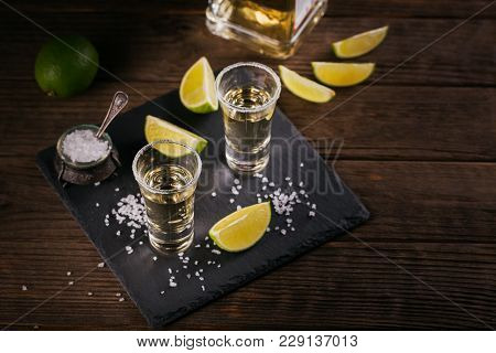 Gold Tequila Shot With Lime And Sea Salt On Black Table. Top View