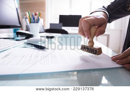 Businessperson Stamping Approved On Contract Paper