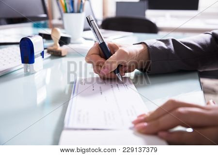 Businessperson Signing Cheque In Office