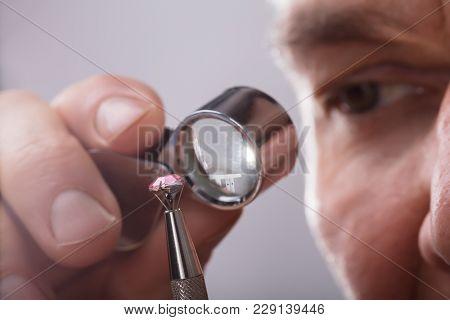 Person Checking Diamond Through Magnifying Loupe