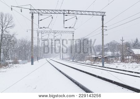 Winter And Snowstorm On The Railroad Tracks. Strong Wind And Snowfall, Snow-covered Rails And Poor V