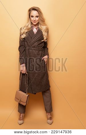 Fashion, people and lifestyle concept: Beautiful woman long blond curly hair wear cashmere coat and holding handbag.