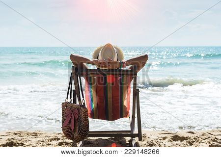 Happy Woman Sitting On A Deck Chair At The Beach,relax On The Tropical Beach. Travel Concept