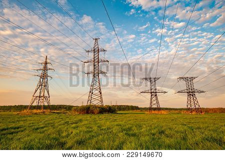 Transmission Towers In The Green Field At The Background Of The Dawn Sky. High-voltage Power Line Ag