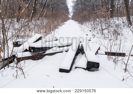 The Disassembled Old Abandoned Railway Track In The Winter Forest. A Bunch Of Sleepers Under The Sno