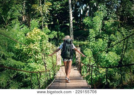 Young Woman With Backpack Traveling Over Hanging Bridge In Forest
