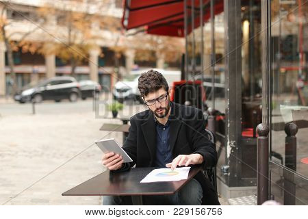 Statistician Working With Diagram Document Papers At Cafe Table Outside In  . Hardworking Man Wears