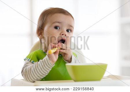 Cute Baby Child Eats Healthy Food Himself With Spoon. Portrait Of Happy Kid Boy With Bib In High Cha