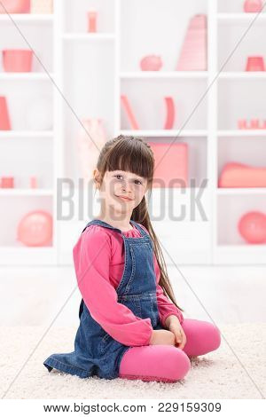 Proud Little Girl Sitting In The Middle Of The Room