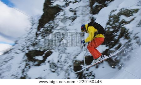Freerider In A Bright Suit Jumps From A Steep Descent On Alpine Skiing, Slow Motion.