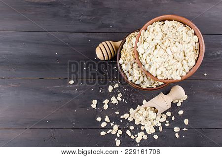 Oat Flakes  In Ceramic Bowl,  In Wooden Scoop And Wooden Spoon For Honey On Dark Vintage Wooden Back