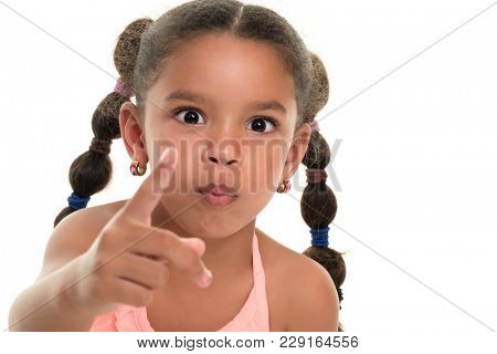 Small multiracial girl pointing to the camera with her index finger - Isolated on white