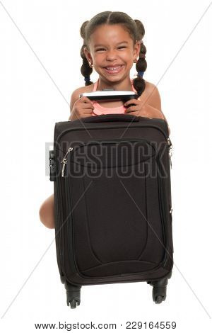 Small multiracial girl  with a travel suitcase and laughing - Isolated on white