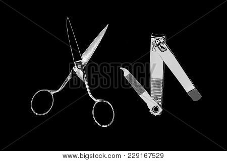 Silver Scissors And Cut Nails On A Black Background