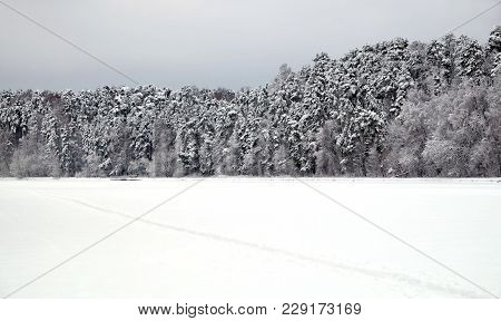 Beautiful Landscape With Long Straight Snow-covered Path On The Edge Of The Forest And Frozen River