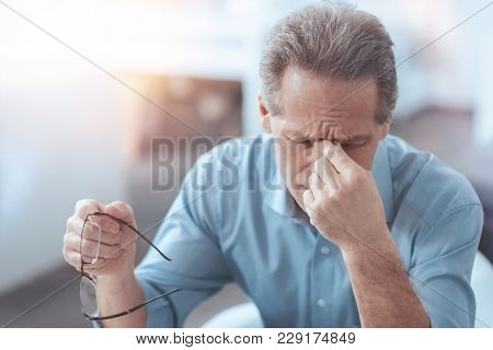 Feeling Tired. Nice Pleasant Senior Man Taking Off His Glasses And Holding The Bridge Of Nose While