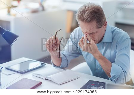 I Need Some Rest. Sad Tired Exhausted Man Holding His Glasses And Rubbing His Bridge Of Nose While F