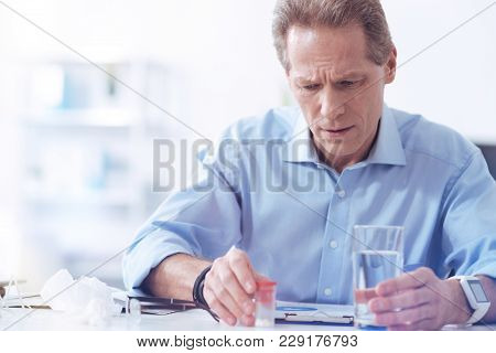 Stress At Work. Sad Cheerless Nice Man Sitting In His Office And Taking Pills While Being At Work