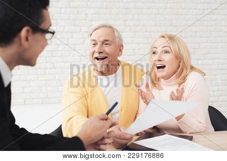 A Couple Of Old People At A Reception With A Realtor. The Old People Are Happy And Smiling, The Real