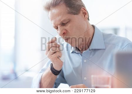 Seasonal Allergy. Cheerless Unhappy Nice Man Holding A Paper Tissue And Wiping His Nose While Having