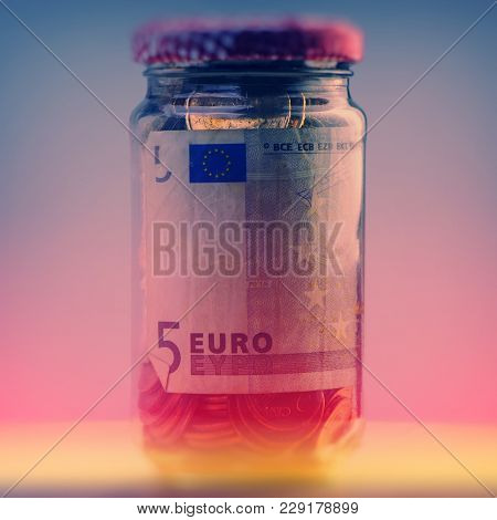 Closed Glass Jar With Euro Coins And Paper Bills. Closeup. Currency Of The Euro Union. Ticket, Check