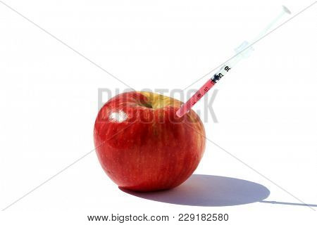 Red Apple with a Medical Syringe injecting GMO or Growth Hormones. Isolated on white with room for text.