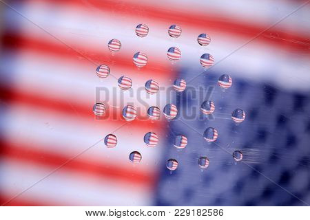 American Flag reflection in water drops. Refraction phenomena of American flag in water drops on glass. backgrounds and textures.