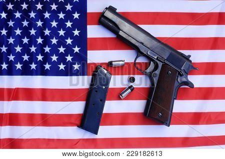 1911 . 45 caliber pistol complete with clip and shells on a American flag. 2nd Amendment Rights to Bear Arms versus Gun Control controversy concepts.