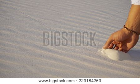 Close-up of face and hands of young Muslim man Arabian Sheikh who takes sand into hand and blows small white grains of sand through fingers, guy smiles and looks out into distance of bottomless desert on hot summer day. Swarthy, handsome Muslim with short poster