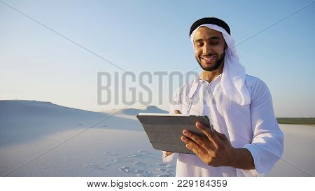 Portrait Of Stately Arabian Sheikh Man Who With Smile On Face Holds Tablet In Hands. Guy Looks Aroun