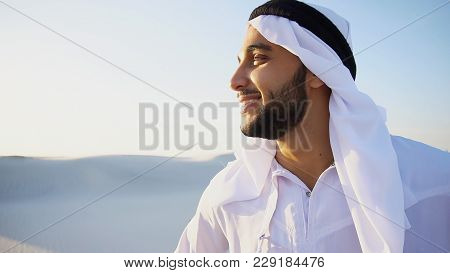Close-up Portrait Of Handsome Muslim Young Man Who Smiles And Looks Around, Watching Beauty Of Natur