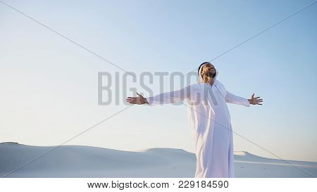 Stately Young Male Arab Man In Good Mood Conducts Financial Training Of Money, Smiles And Laughs Joy