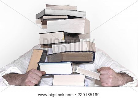 A Pyramid From Books And A Man Behind It