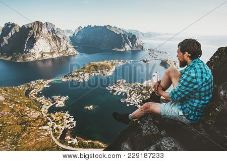 Traveler Man Sitting On Cliff Edge Alone Traveling In Norway Lifestyle Adventure Outdoor Summer Vaca