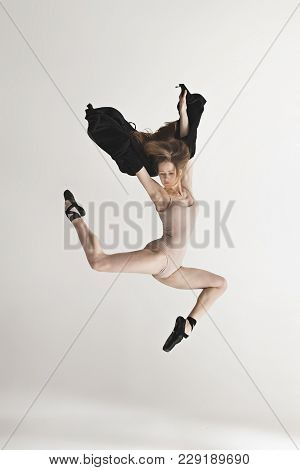 Young Beautiful Dancer In Beige Swimsuit Dancing On Gray Studio Background. Front View. Young Female