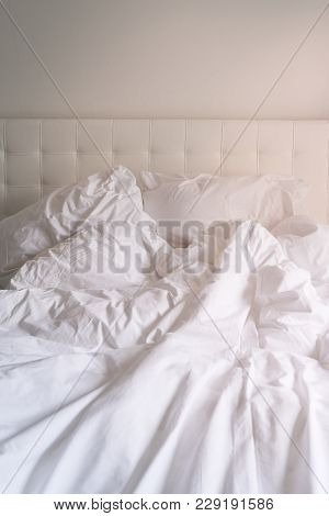 Unmade Bed With Plain White Bed Linen In A Close Up View Of A Rumpled Duvet, Pillows And A Padded He