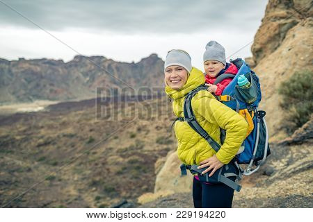 Family Hiking With Baby Boy Travelling In Backpack. Hiking Adventure With Child On Autumn Family Tri