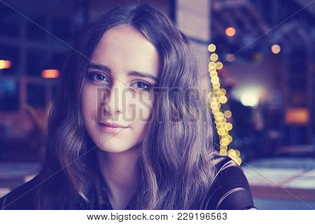 Beautiful Girl Is Sitting In The Cafe. She Has Big Brown Romantic Eyes. With Nice Brown Long Hair. W