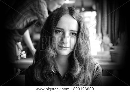Pretty Smiling Girl Sitting In A Cafe. She Has Big Brown Romantic Eyes. With Nice Brown Long Hair. W