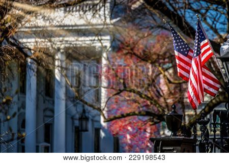 The Sun Shining On Two Flags On The Fence Near The White House In Washington Dc.