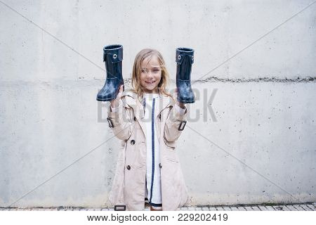 Girl  Pouring Water From Her Boot And Playing On The Rain.
