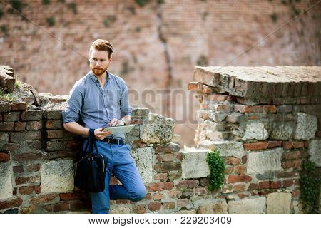 Handsome Businessman Relaxing Outdoors In City Park