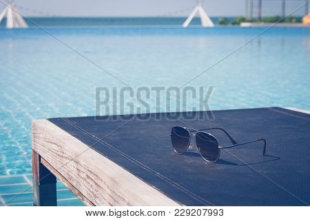 Summer Vacation And Holiday Concept :sunglasses Put On Wooden Daybed In Swimming Pool With Seascape