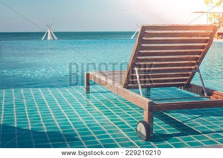 Vacation And Holiday Concept : Close Up Wooden Daybed In Swimming Pool For Sunbathing And Resting In