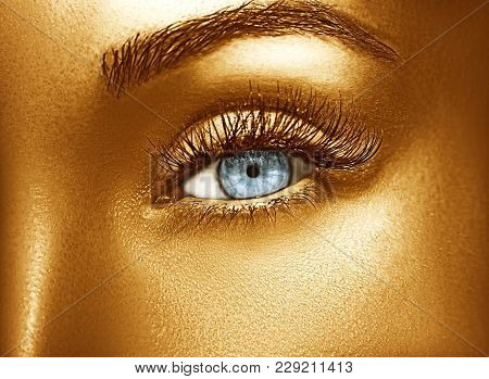 Glamour Shiny Gold Professional Makeup. Beautiful Golden Skin Close Up