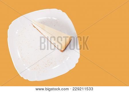 Classic Cheesecake On A White Plate Isolated On Orange