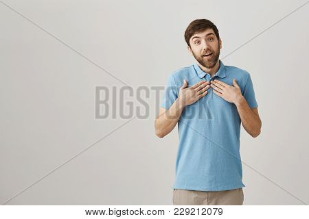 I Am Touched To My Heart. Studio Shot Of Pleased Lovely Bearded Caucasian Guy Holding Hands On Chest