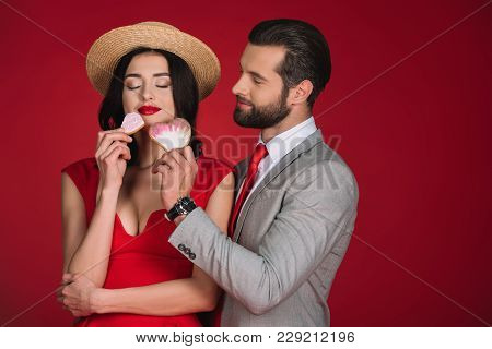 View Of Girlfriend Sniffing Cookies Isolated On Red