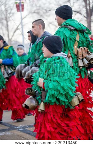Pernik, Bulgaria - January 26, 2018: Teen Boy Dances And Jumps In Ecstasy With Huge Brass Bells To E