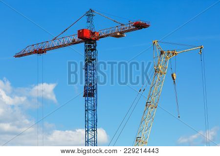Two Construction Cranes. Tower Crane And Mobile Construction Crane Against Blue Sky Background.